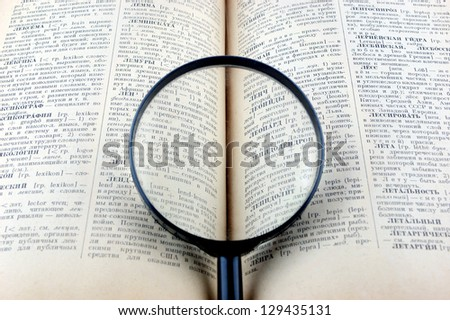 Old book with magnifying glass - stock photo