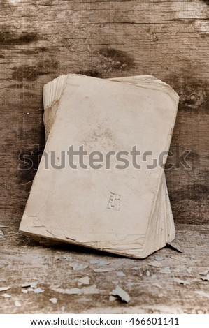 old book with paper waste on wooden background