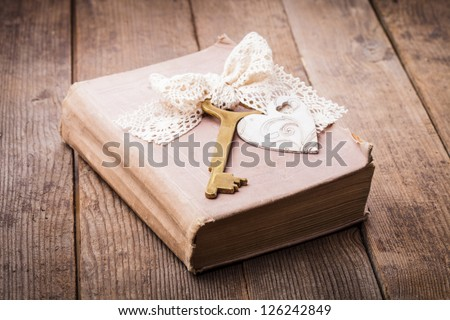 Old book with vintage key and wooden heart, memories concept - stock photo