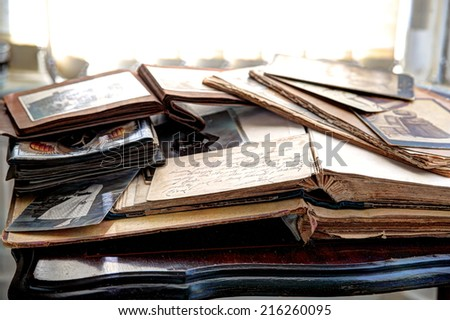 Old books, albums and photos on antique table. - stock photo