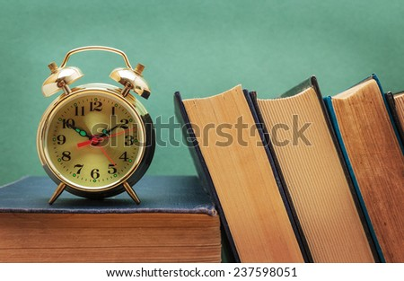 old books and alarm clock - stock photo