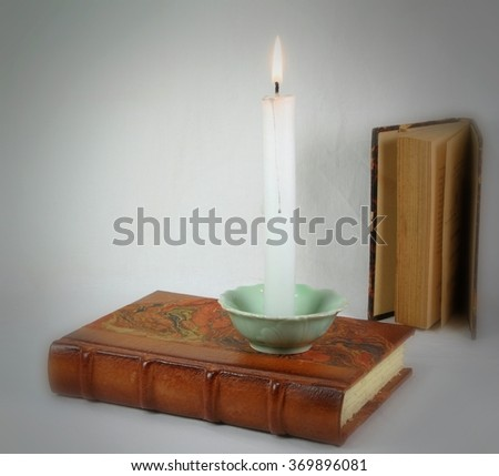 Old books and candle. Knowledge concept. - stock photo