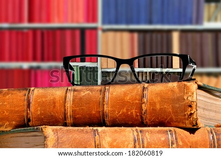 Old books and eye glasses with sharp vision through them on the books against the indistinct (unsharp, not in focus) background - Concept of visual acuity return  - stock photo