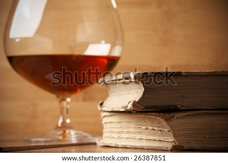 Old books and glass of cognac on wood background. Selective focus on front edge of books.