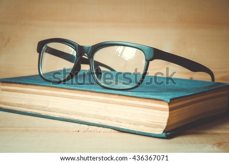 Old books and glasses on a wooden table with filter effect retro vintage style - stock photo