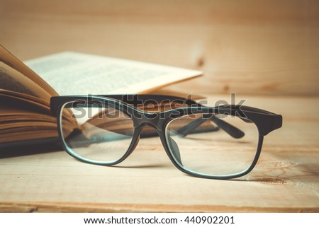 Old books and glasses on a wooden table with filter effect retro vintage style