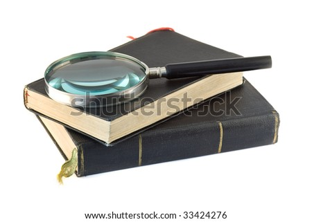 Old Books and Magnifying glass isolated on white