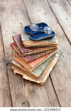Old books and old eyeglasses on wood background - stock photo