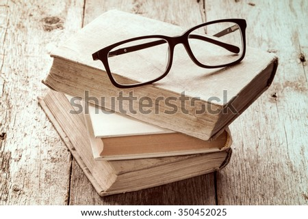 Old books and reading glasses on the wooden background - stock photo