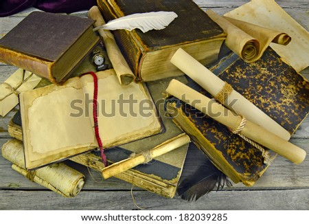 Old books and scrolls background with quill pens - stock photo