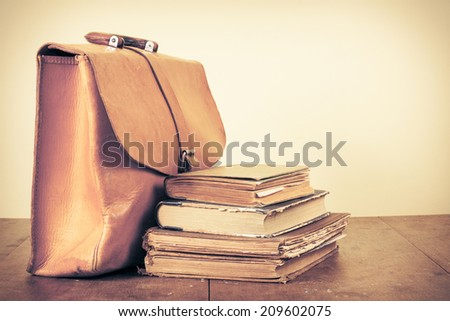 Old books and vintage leather school bag on table - stock photo