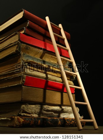 Old books and wooden ladder, on black background - stock photo