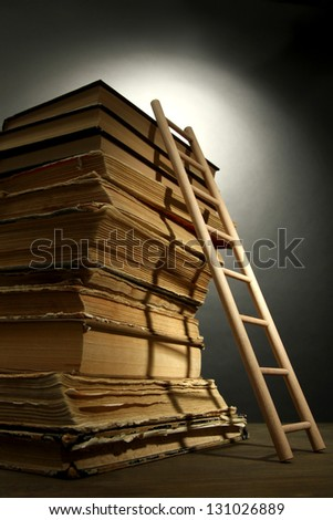 Old books and wooden ladder, on grey background - stock photo