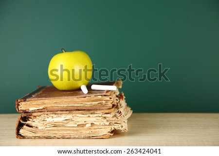 Old books, apple and chalk on blackboard background - stock photo