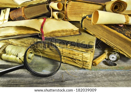 Old books background with enlarging hand glass and pocket watch - stock photo