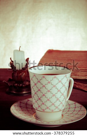 Old books, cup of coffee, candy and ancient candle on the table. Shallow depth of field. Selective focus. Toned. - stock photo