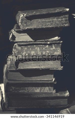 Old books for sale at flea market in Paris (France). A game of light and shadow. Selective focus. Aged dark photo. Black and white. - stock photo
