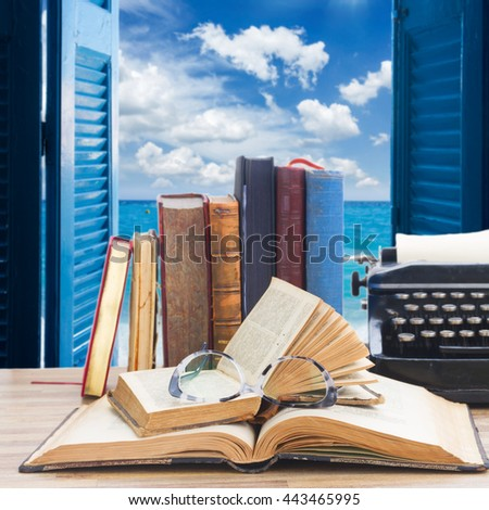 Old books, glasses and typewriter over open window to sea and sky background - writting and publishing concept - stock photo