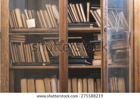 Old books in a vintage library shelfs - stock photo