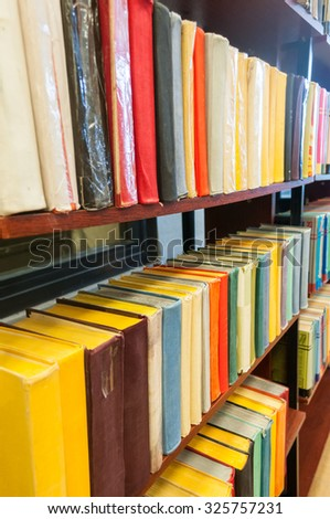 Old books in wooden bookcases in library - stock photo