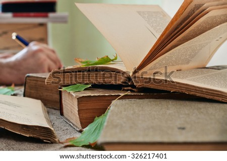 Old books. Old open book close up with autumn leaves on the table. In the background a man hand writing in a notebook. Copy space - stock photo