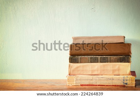 Old books on a wooden table. retro filtered image  - stock photo