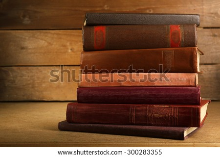 Old books on shelf, close-up, on wooden background - stock photo