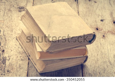 Old books on wooden background in vintage tone color