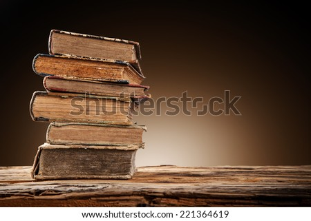 Old books on wooden planks with blur shimmer background - stock photo