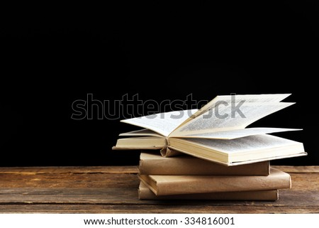 Old books on wooden table against black background