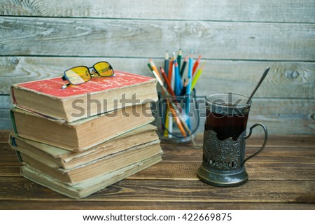 Old books. Pile of old books. Old books on a wooden table against a wooden wall. - stock photo