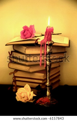 Old books, roses and a candle in sepia tone