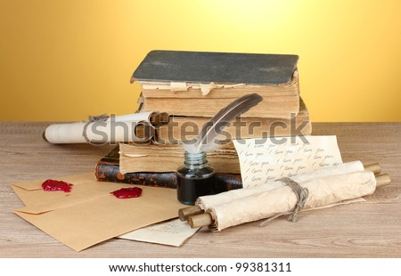 old books, scrolls, feather pen and inkwell on wooden table on yellow background - stock photo