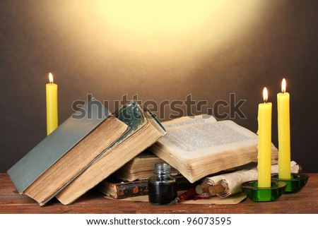 old books, scrolls, ink pen inkwell and candles on wooden table on brown background - stock photo