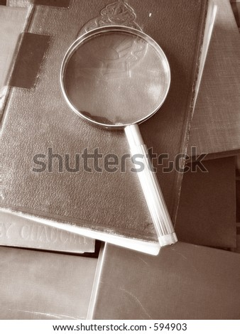 Old books with magnifying glass - stock photo