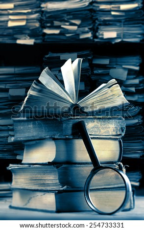 Old books with magnifying glass in archive - stock photo
