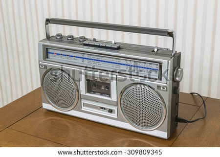 Old boom box radio cassette recorder on wood table. - stock photo