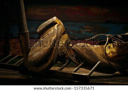 Old boots and rake on wood textured background.  - stock photo