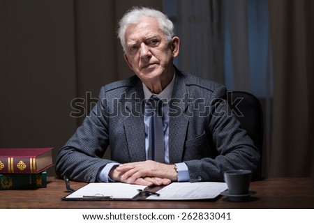 Old boss working overtime at office room - stock photo