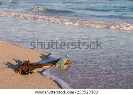 Old bottle lay on the beach with sea plant and wave move in - stock photo