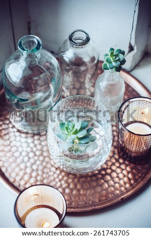 Old bottles, candles on a copper vintage tray, vintage home decor - stock photo