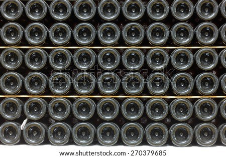 Old bottles of wine in rows in wine cellar - stock photo