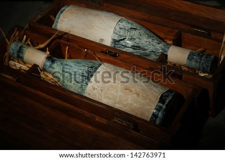 Old bottles of wine in wooden boxes, on dark brown background - stock photo