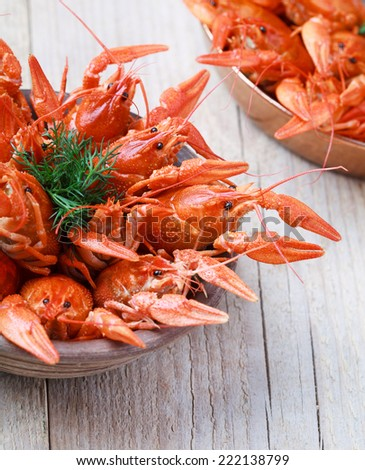 Old bowl with red boiled crawfish on a wooden table in rustic style, close-up, selective focus on one crawfish - stock photo
