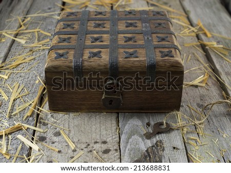 Old box with lock on the wooden background - stock photo