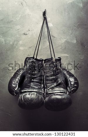 old boxing gloves hang on nail on texture wall. Retirement concept - stock photo