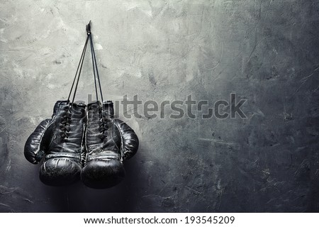 old boxing gloves hang on nail on texture wall with copy space for text. Retirement concept - stock photo