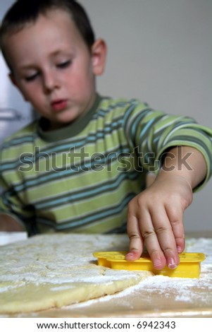 old boy cutting out cookies - stock photo