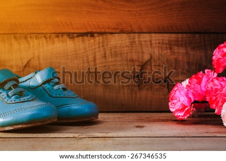 old boy shoes on wooden floor with carnation ,abstract background to first step concept, and Thank you mother day.vintage color photo. - stock photo