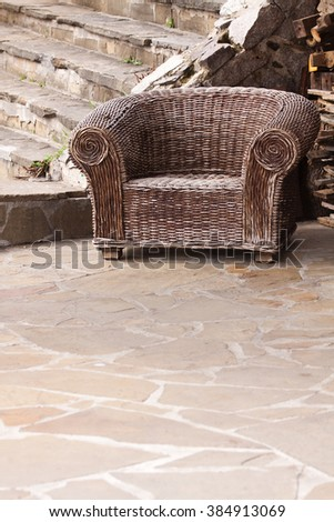 Old braided wicker chair with signs of wear - stock photo